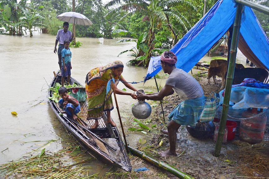 A family bringing their belongings to a makeshift camp in the Morigaon district of Assam, India, on Monday. The monsoon rains have wreaked havoc again this year across India, Nepal, Bangladesh and Pakistan-administered Kashmir, with people, dwellings