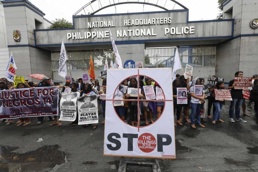 Protesters with signs against extrajudicial killings allegedly committed by police and military hold a rally outside Philippine police headquarters in Quezon on July 17, 2019.