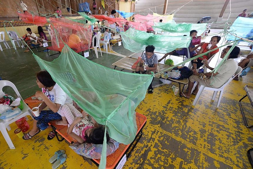 Patients with dengue fever resting under mosquito nets in a gym in Maasin, a town in the Philippine province of Iloilo, yesterday. On Monday, the Philippine Department of Health issued a national alert to warn of an outbreak of dengue fever, with mor