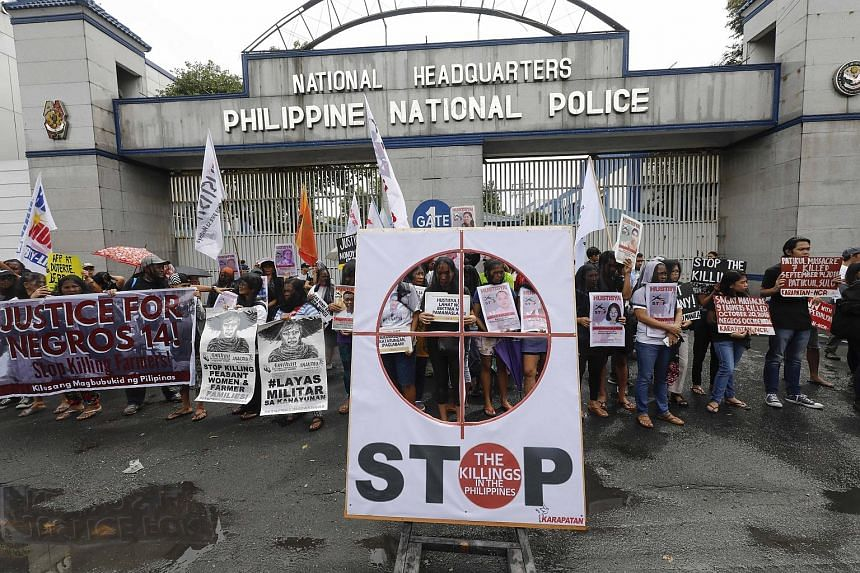 Protesters with signs against extrajudicial killings allegedly committed by the police and military demonstrating outside Philippine police headquarters in Quezon City, east of Manila, on Wednesday.