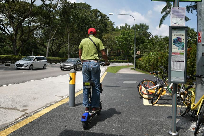 A man on an electric scooter or personal mobility device (PMD) riding on the pavement along Holland Road.