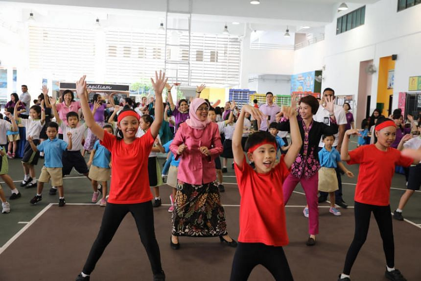 President Halimah Yacob and Ms Low Yen Ling join in the Harmony Dance by students of Punggol Green Primary School at the school's commemoration of Racial Harmony Day on July 19, 2019.