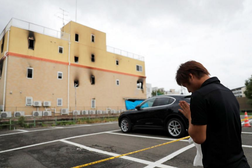 A man paying his respects outside the Kyoto Animation building which was torched by an arson attack in Kyoto, Japan.