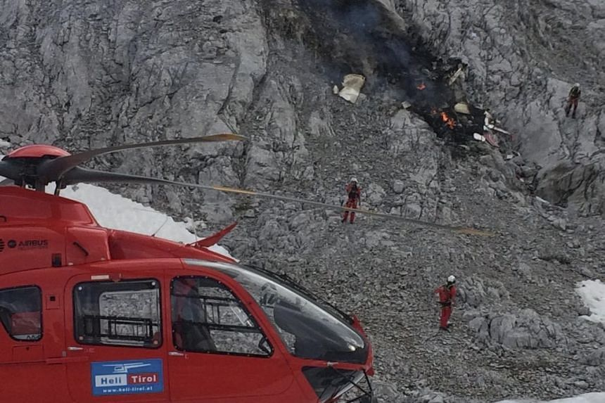 Rescue personnel stand at the scene after a small aircraft crashed on a mountain.