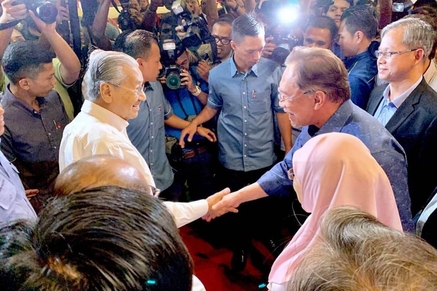 Malaysian Prime Minister Mahathir Mohamad (left) being greeted by Parti Keadilan Rakyat president Anwar Ibrahim on arrival at the party's retreat in Port Dickson on July 19, 2019.