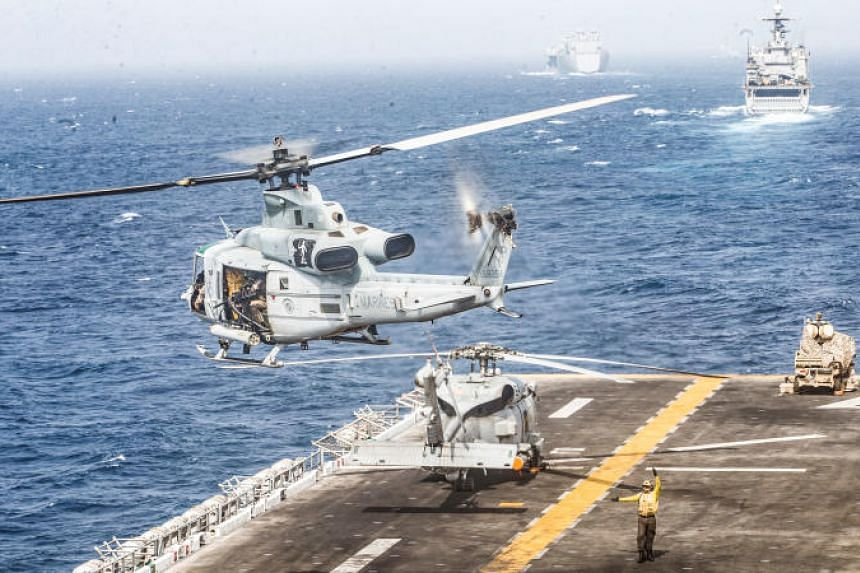 A US Marines UH-1Y Venom helicopter takes off from the flight deck of the US Navy amphibious assault ship USS Boxer during its transit through the Strait of Hormuz in the Gulf of Oman on July 18, 2019.