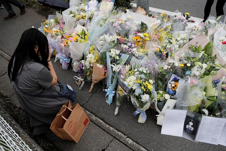 A woman praying at the site of the torched Kyoto Animation building in Kyoto yesterday. Fifteen of the 34 victims of Thursday's arson attack were in their 20s and 11 in their 30s, some joining the company only in April.