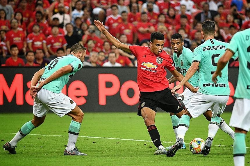Manchester United's 17-year-old forward Mason Greenwood is surrounded by Inter Milan players as he attempts a shot during their match at the National Stadium yesterday.