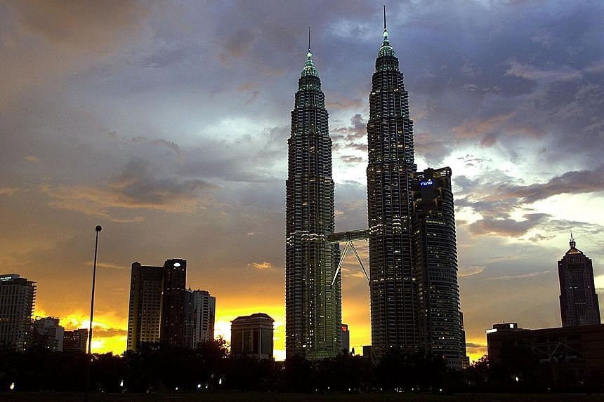 Mr Cesar Pelli's many celebrated works include the Petronas Towers (top) in Kuala Lumpur. His firm was also responsible for the architectural design concept of Ocean Financial Centre (left) in Singapore. PHOTOS: AGENCE FRANCE-PRESSE, ST FILE