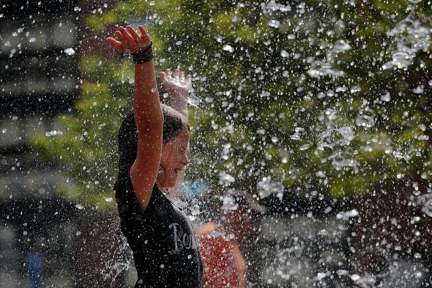 A girl playing in a fountain to keep cool during the heatwave at the Rose Kennedy Greenway park in Boston on Friday. Utility providers in the eastern half of the US expect to have enough resources to meet power demand, but asked people to turn down a