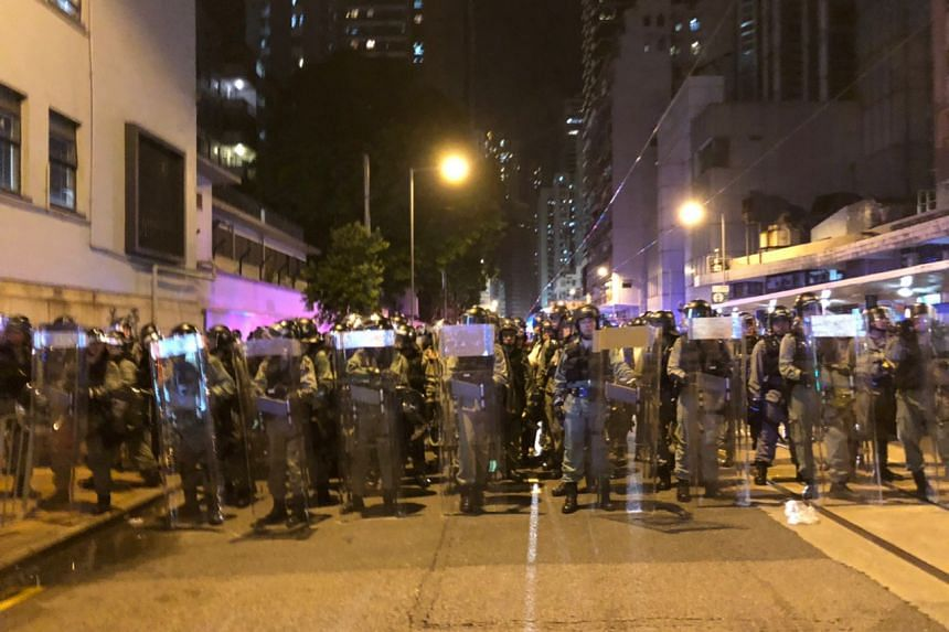 Hong Kong police officers forming a wall while clearing streets in Sai Ying Pun, on July 21, 2019.