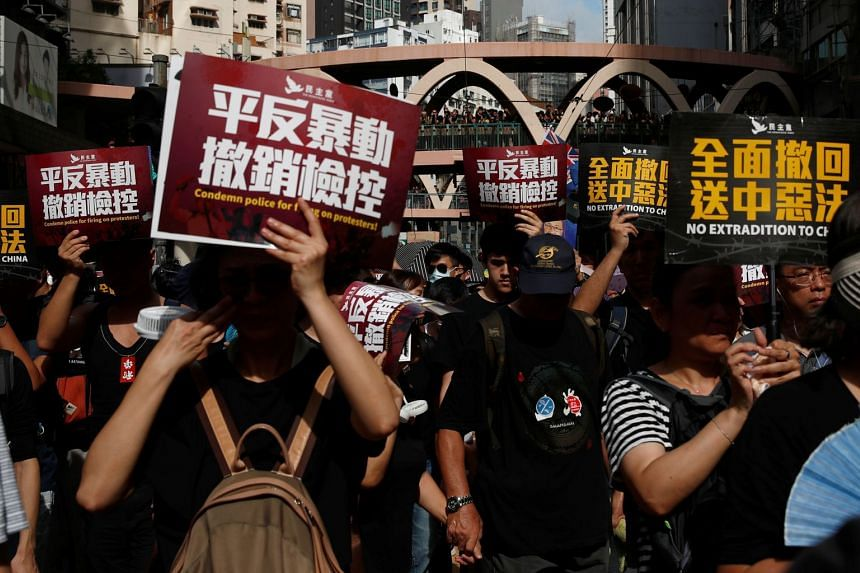 Anti-extradition demonstrators hold banners while marching during a protest in Hong Kong on July 21, 2019.