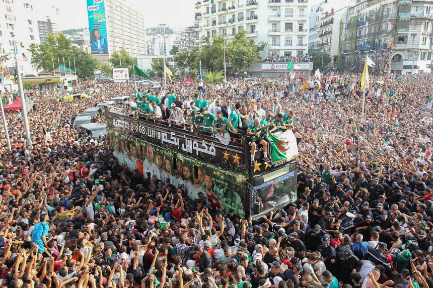 Algerian fans line the streets to see their national team take part in an open-top bus parade in the capital Algiers.
