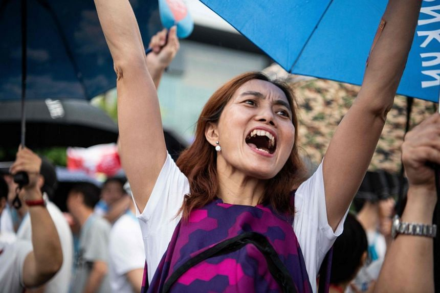 A woman cheers at a pro-police rally in Tamar Park outside the government headquarters in Hong Kong.
