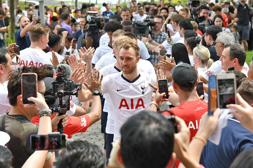 Christian Eriksen giving fans high-fives upon arriving to attempt and set a record for the fastest passes of a football involving 100 people in Singapore.