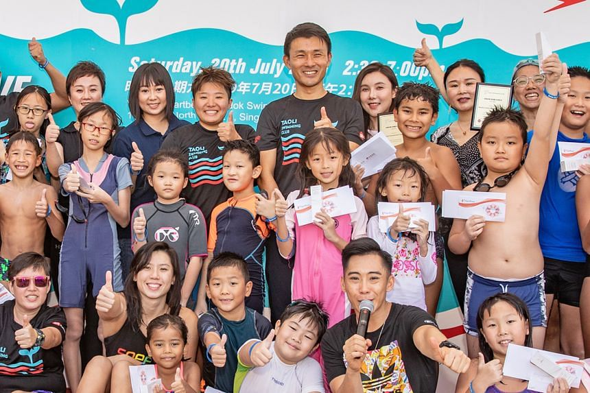 Tao and her swimming club which bears her name at the Swim For Love Family Fun Day at Heartbeat @Bedok yesterday. The community event was organised by her club for about 60 children and was also attended by Senior Parliamentary Secretary for Transpor