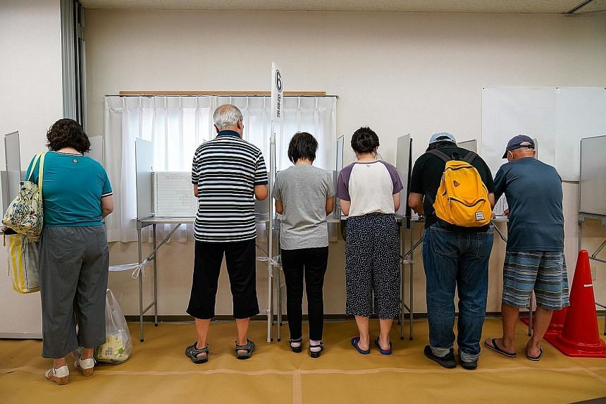Voters filling in ballot papers at a polling station in Yokohama during Japan's Upper House election yesterday.