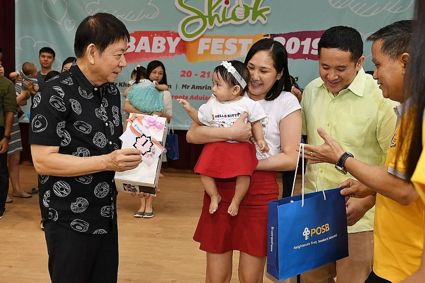 Transport Minister Khaw Boon Wan presenting the top prize in a baby lookalike contest to Madam Venus Bancoro Catibog and her baby Maven Emmanuelle Bancoro Catibog, together with Senior Parliamentary Secretary for Home Affairs and Health Amrin Amin (s