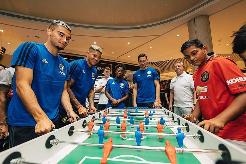 United players (from left) Andreas Pereira, Marcos Rojo, Angel Gomes and Matteo Darmian playing table football with fans at The Maybank Manchester United Tour 2019 held at Suntec City.