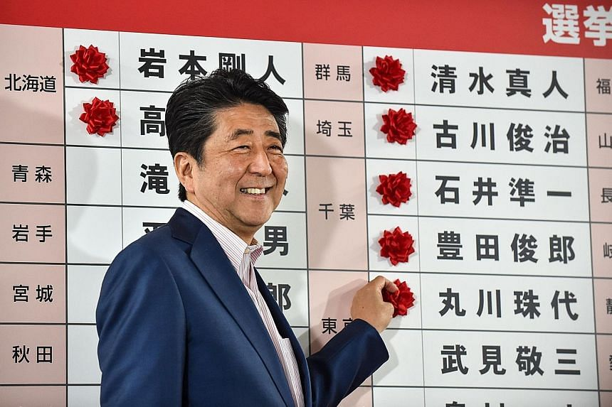 Japanese Premier Shinzo Abe highlighting the names of winning candidates with paper flowers at the Liberal Democratic Party's headquarters in Tokyo yesterday.