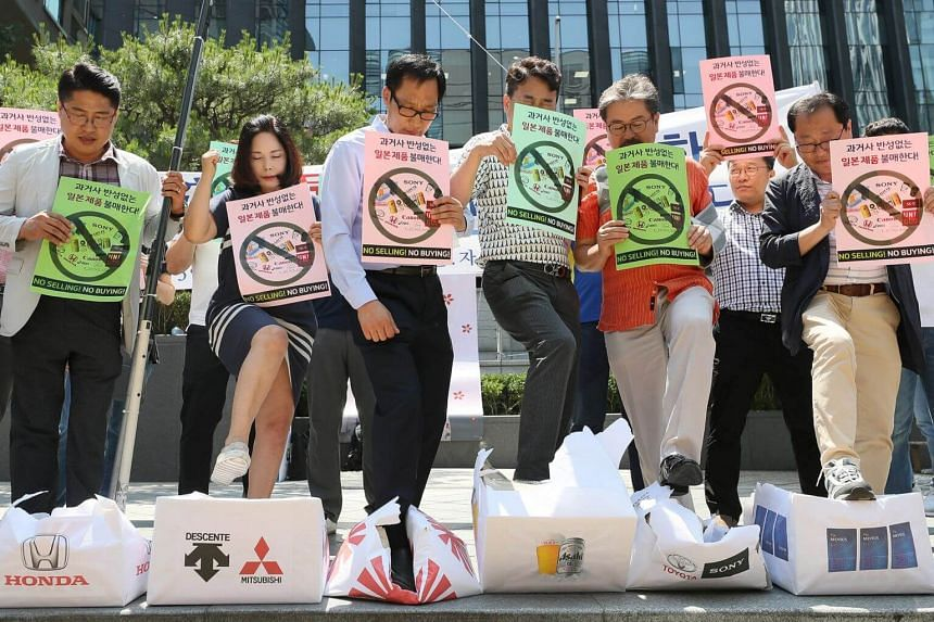 South Korean merchants step on boxes bearing logos of Japanese products during a rally to declare a boycott of Japanese goods in Seoul, South Korea, on July 5, 2019.