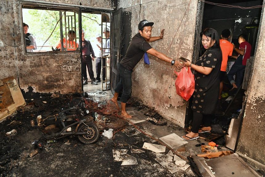 Occupants of the affected unit salvaging their belongings after the fire was extinguished.