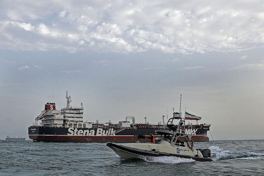 An Iranian official talking to crew members inside the Stena Impero on Sunday. Iran says the tanker was captured after it collided with a fishing boat, but Britain says there is no evidence of that. Iranian Revolutionary Guards patrolling around the