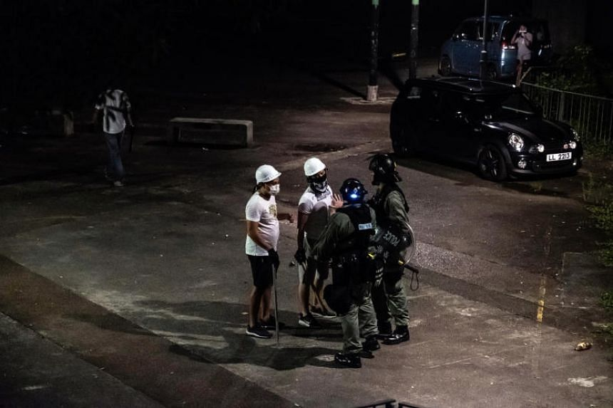 Riot police officers talk to men armed with sticks outside a train station in Yuen Long, a Hong Kong border town near mainland China, on June 21, 2019.