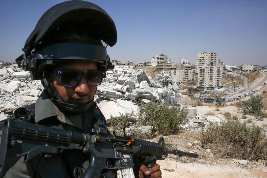 A member of the Israeli border police stands guard in front of buildings demolished by Israel in the West Bank village of Dar Salah.