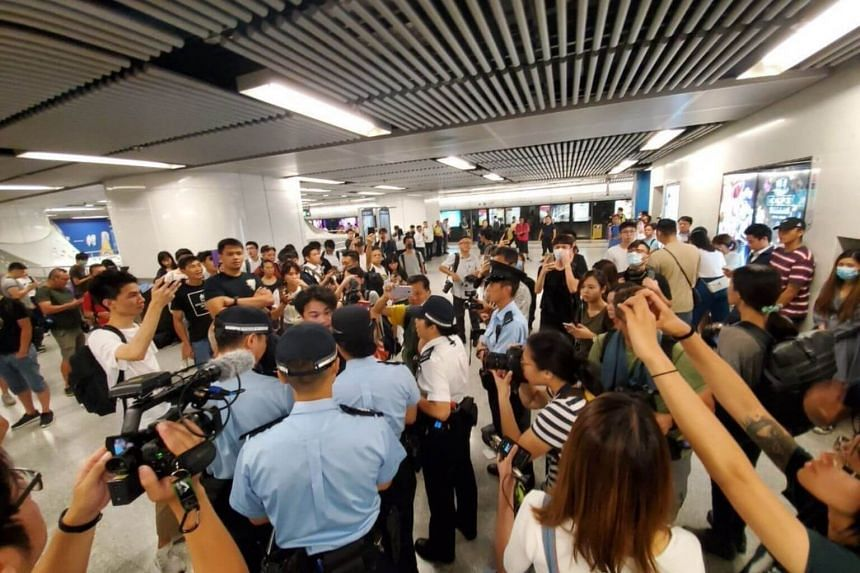 A photo on social media showing an exchange between a commuter and police at an MTR station in Hong Kong.