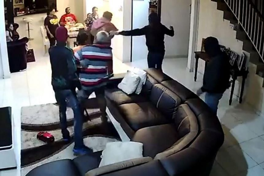 In the video, eight people can be seen lounging in the hall watching TV and seated at a table, when three masked men armed with machetes entered the house.