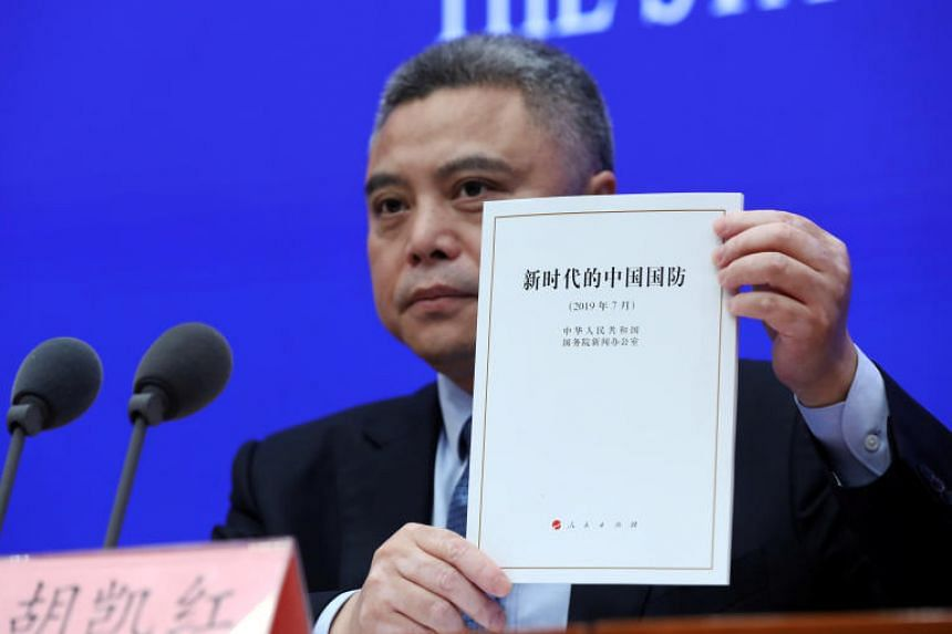 """Mr Hu Kaihong, spokesman for China's State Council Information Office, with a copy of the White Paper entitled """"China's National Defence in the New Era"""" during a news conference in Beijing on July 24, 2019."""