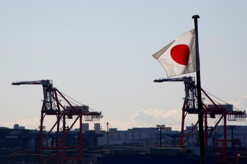 Japan's national flag seen in front of containers and cranes at an industrial port in Tokyo.