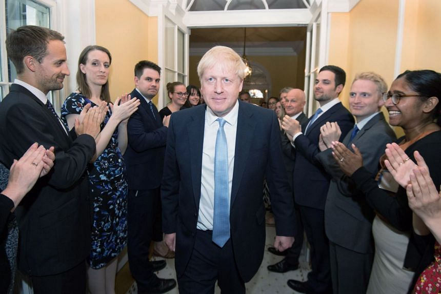 Boris Johnson is welcomed as he enters 10 Downing Street in London.