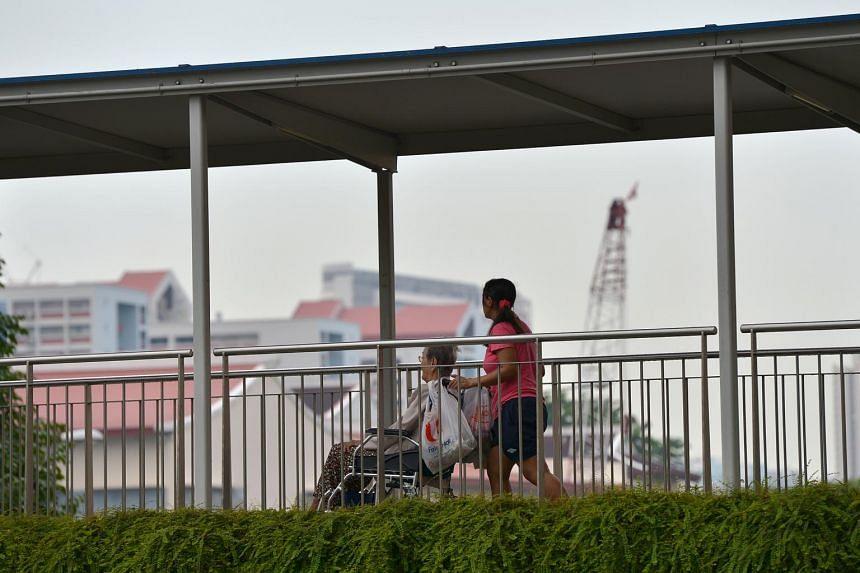 A domestic helper pushing an elderly woman in a wheelchair at an overhead bridge.