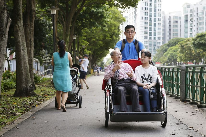 Volunteer Chua Beng Wan giving a ride to retiree Lee Kee Siang and his granddaughter Janet on Oct 8, 2016. ST FILE PHOTO