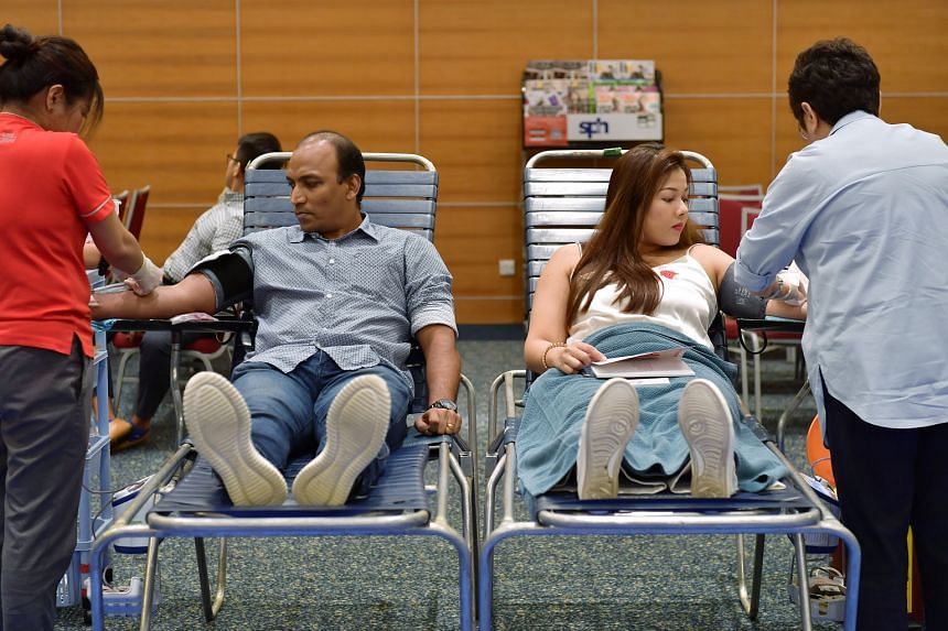 Singapore Press Holdings staff Sajo Kuttikkat Johny, senior manager (Adtech), and Nisha Basand Ram, assistant manager of marketing and circulation, donating blood during SPH Red Apple Day at the SPH Auditorium yesterday. Some 119 units of blood were