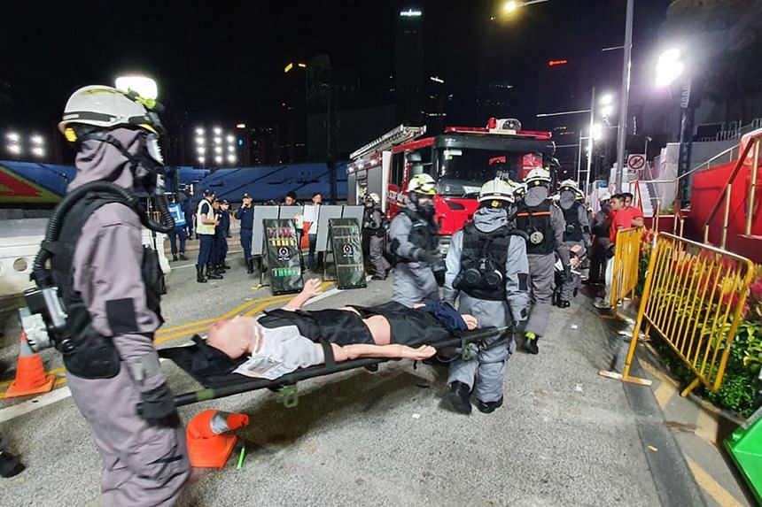 "SCDF officers in protective suits moving ""casualties"" to the decontamination point at the Padang during the exercise early yesterday morning."