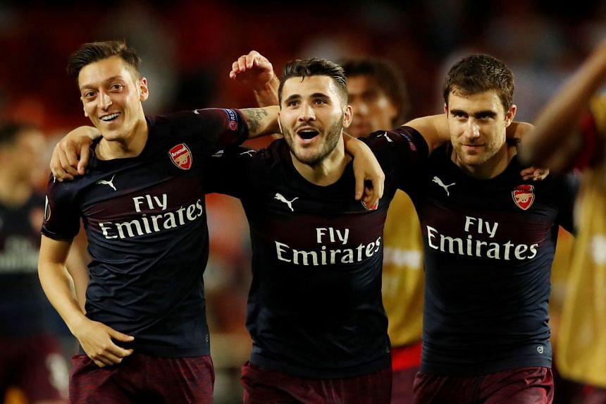 Arsenal's Mesut Ozil, Sead Kolasinac and Sokratis Papastathopoulos celebrate after a match.
