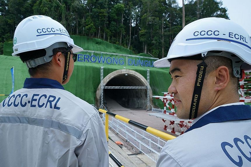 China Communications Construction Company workers standing in front of a tunnel being built for the East Coast Rail Link project in Dungun, Terengganu, yesterday. Malaysia relaunched the project after a year-long suspension and following a deal to sl