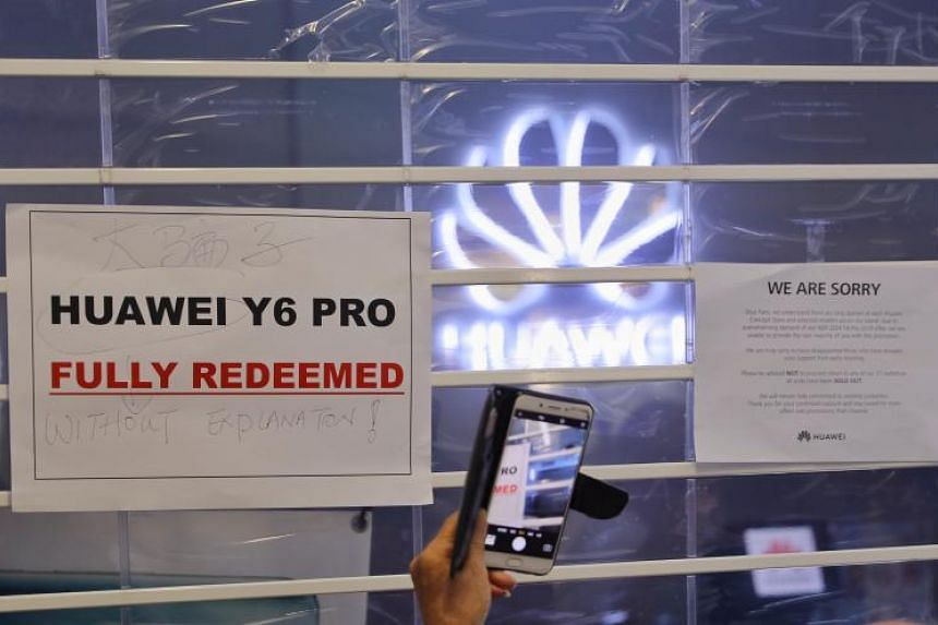 A sign on the shutter stating that the $54 smartphone promotion had ended at the Huawei store at NEX shopping mall on July 26, 2019.