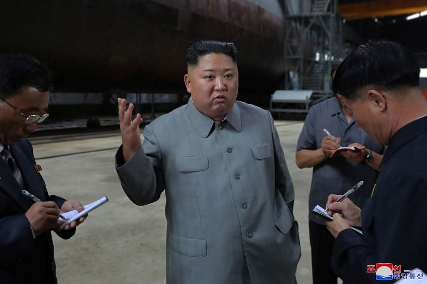 Kim (centre) speaks to the media during an inspection of a newly built submarine.