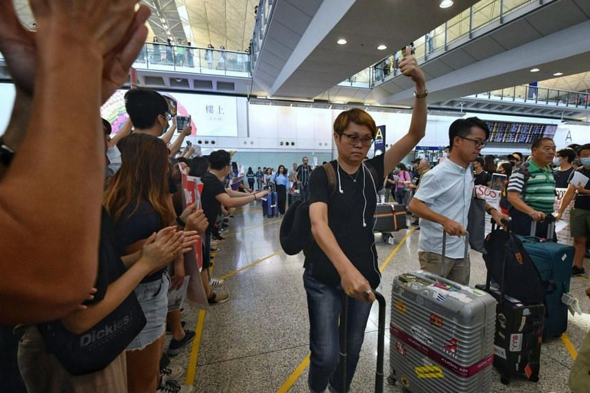 A passenger giving the thumbs up to the protesters at the arrival halls of Hong Kong airport.