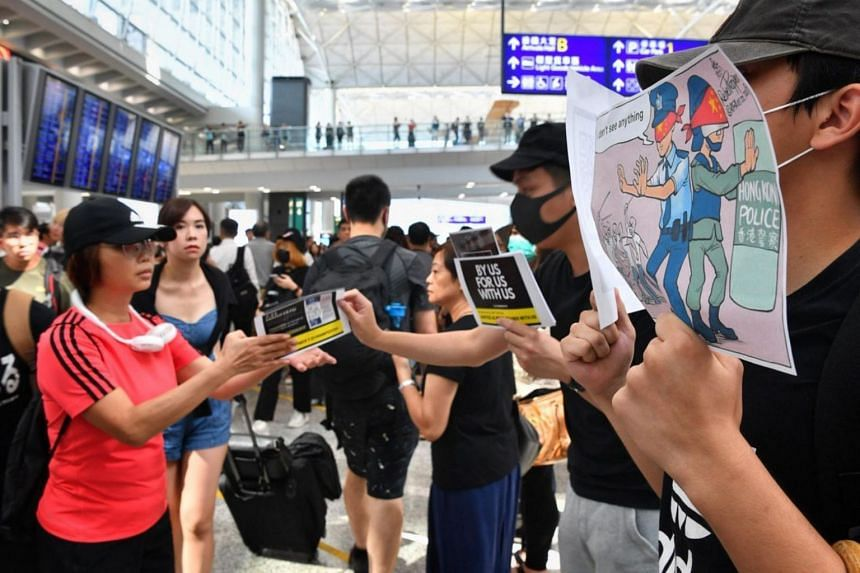 Protesters giving out pamphlets to passengers arriving at Hong Kong airport.