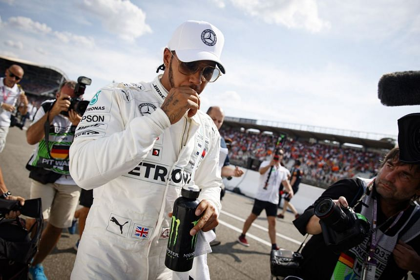 Hamilton reacts after taking pole position for the German grand prix.