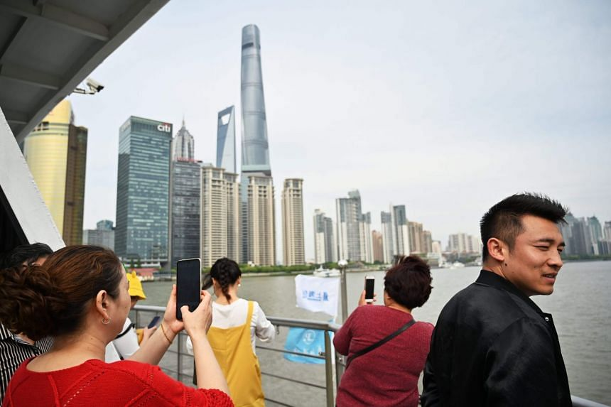 People travel on a sightseeing boat along the Huangpu River as it passes the skyline of Shanghai's financial district.