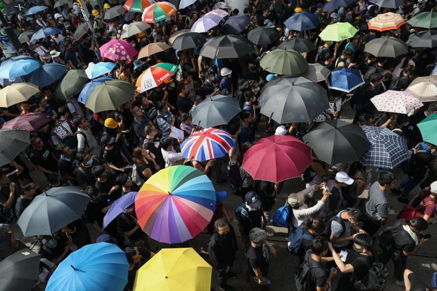 Protesters carrying umbrellas joining a demonstration in Yuen Long, Hong Kong, on July 27, 2019.