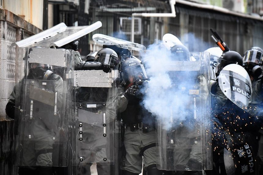 A police officer firing a tear gas round at protesters during a confrontation in Yuen Long on July 27, 2019.