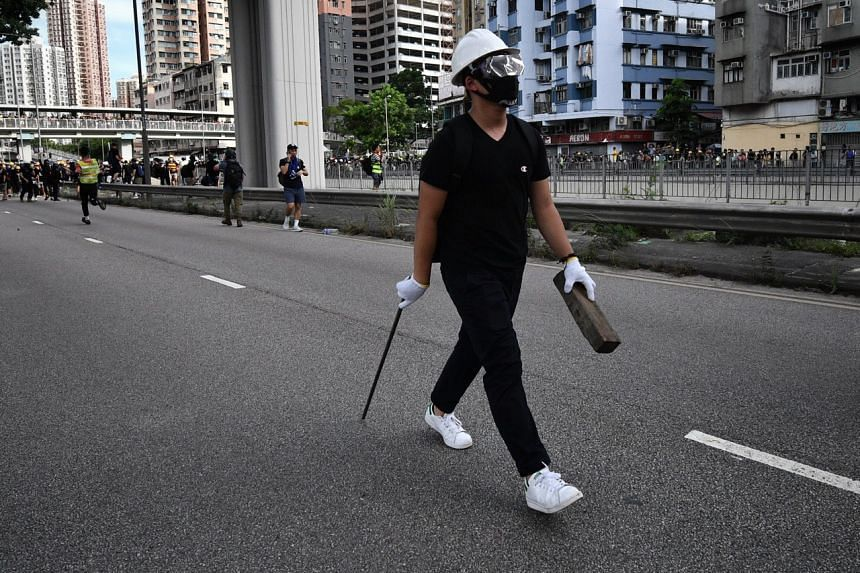 A protester carrying a stick and a brick walking on the road as other protesters demonstrate, on July 27, 2019.