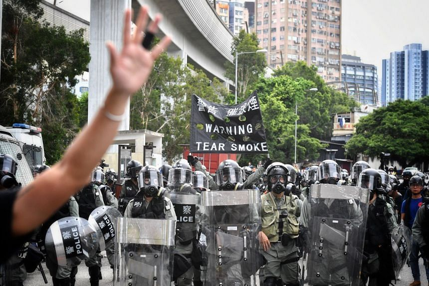 Police officers warning protesters that they are deploying tear gas, during a mass rally in Yuen Long on July 27, 2019.